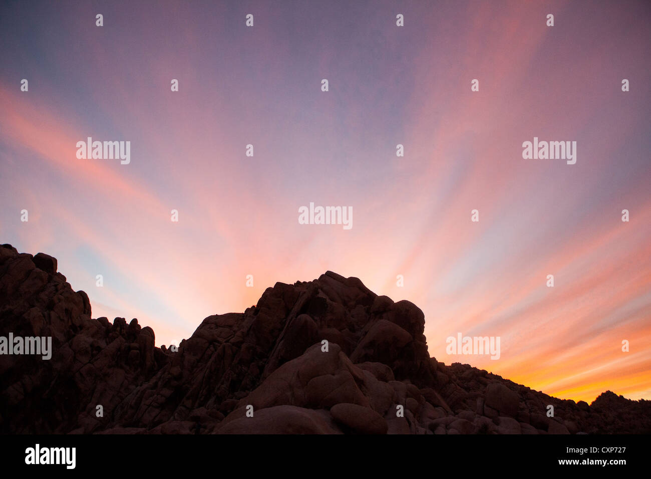 dramatic sunset in the desert with silhouette of rocks and mountains. - Stock Image
