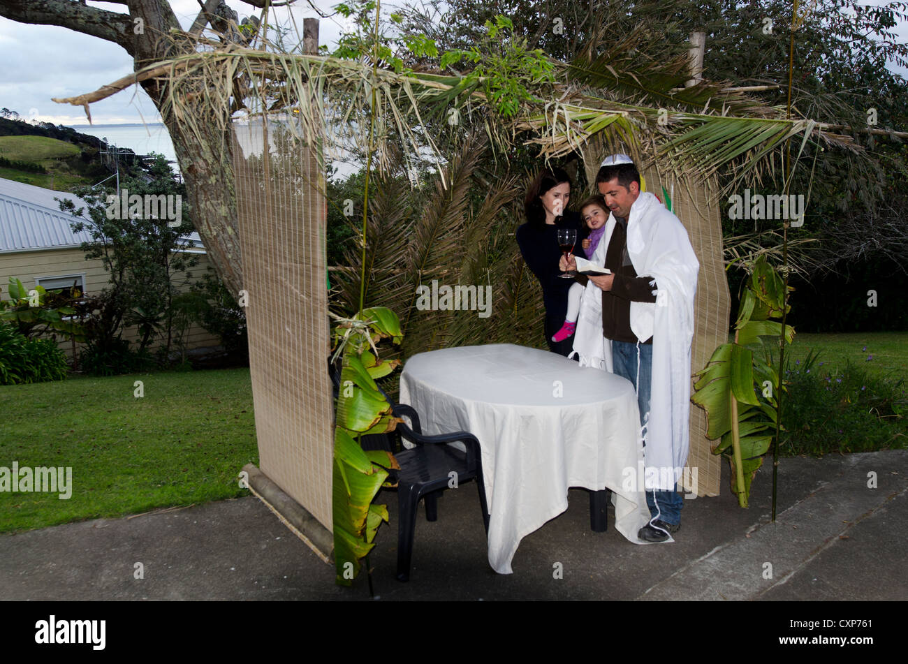 Young Jewish family prays at the Sukkah for the Jewish festival of Sukkot. - Stock Image