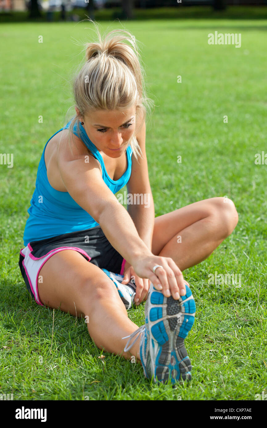 Woman stretching / warming up exercises - Stock Image