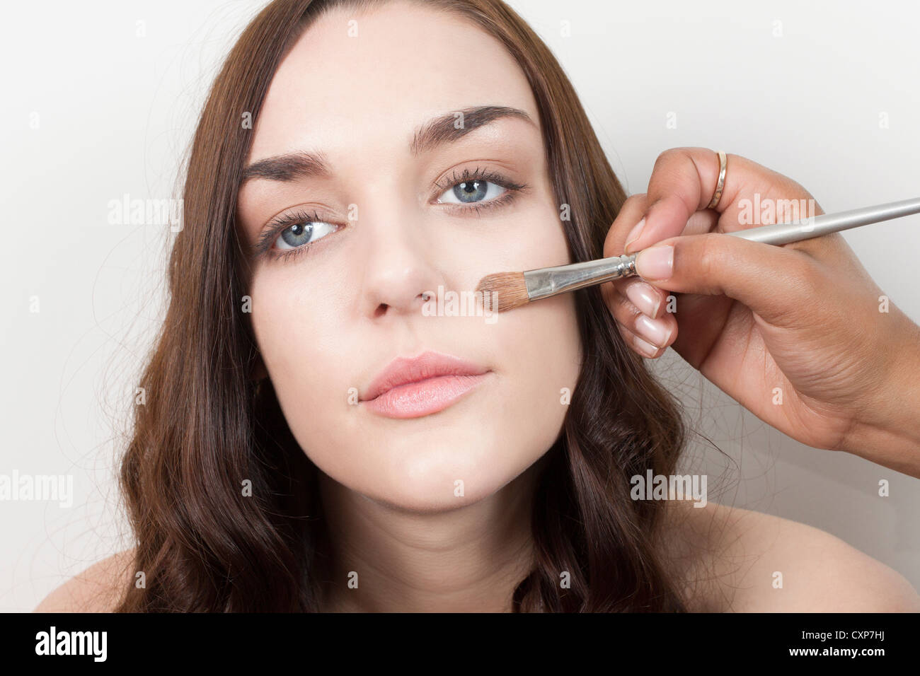 Woman having makeup applied by a make up artist - Stock Image