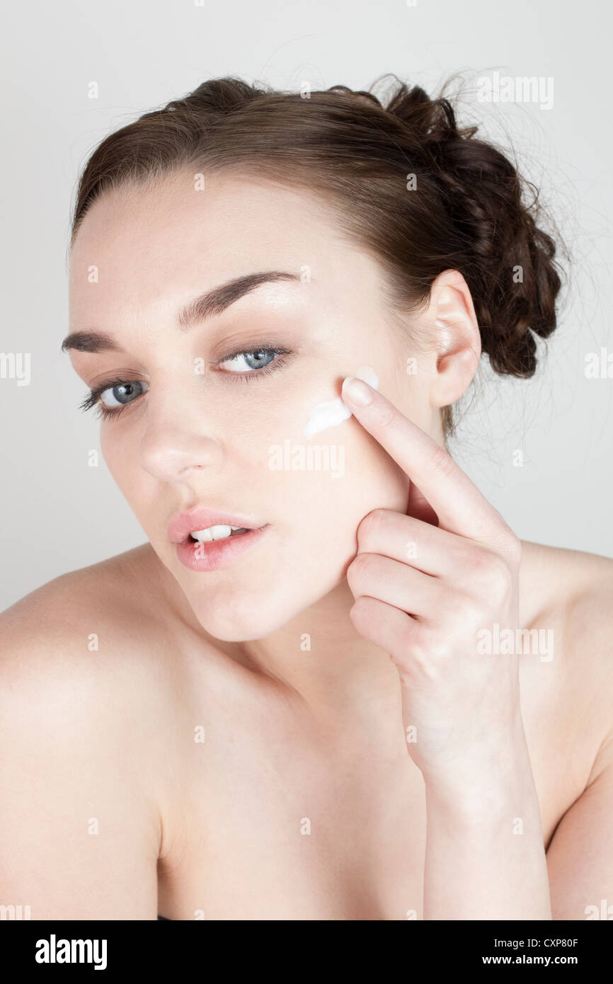 Woman looking in mirror and applying face cream - Stock Image