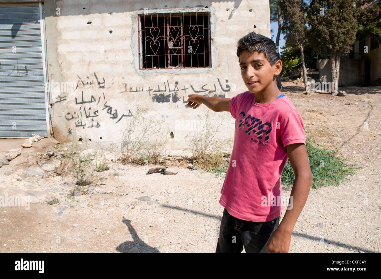 A Syrian refugee points to anti-Assad graffiti in the northern Lebanese region of Wadi Khaled on the Syria-Lebanon - Stock Image