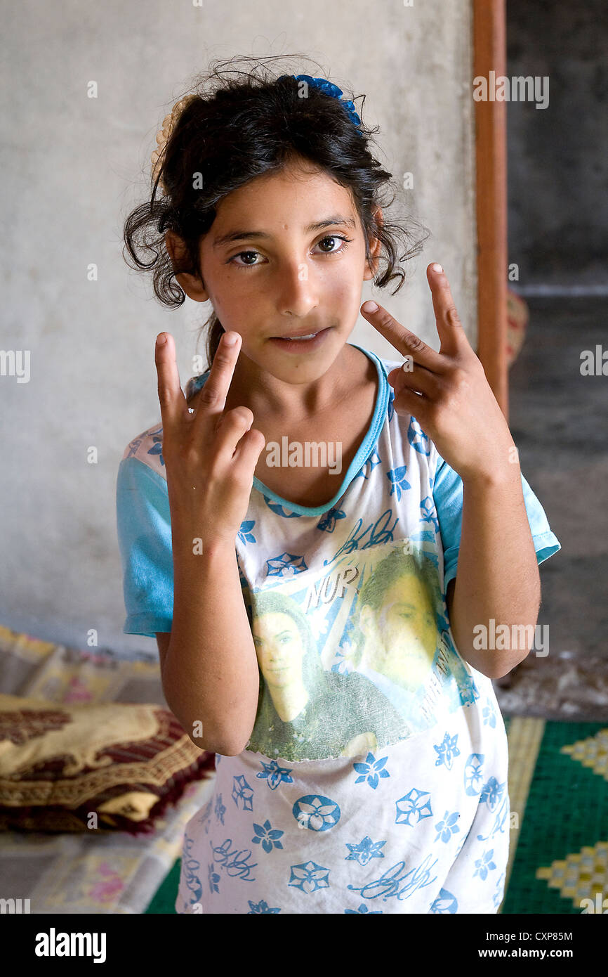A Syrian refugee child holds her fingers up in the victory sign, in the Wadi Khaled region of Northern Lebanon. - Stock Image