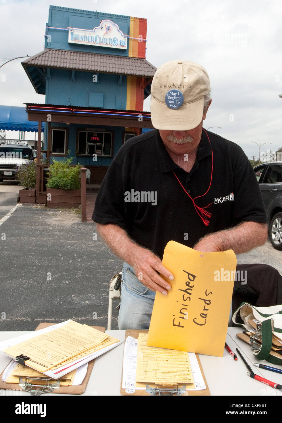 White male volunteer voter registrar sets up registration table in Austin, TX, shopping center parking lot before - Stock Image