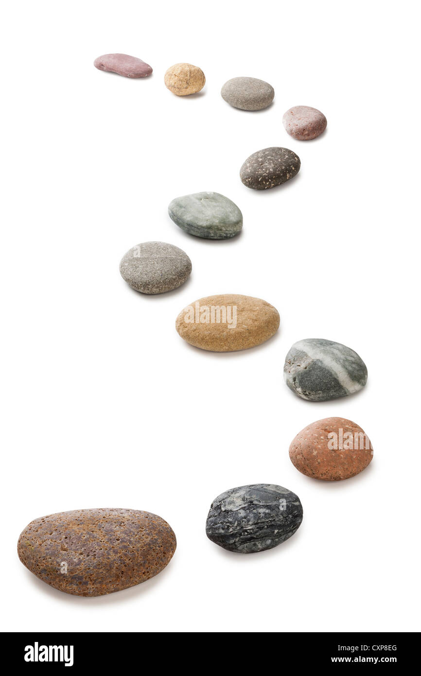 A curving row of pebbles representing stepping stones, isolated on white with clipping path around pebbles. - Stock Image