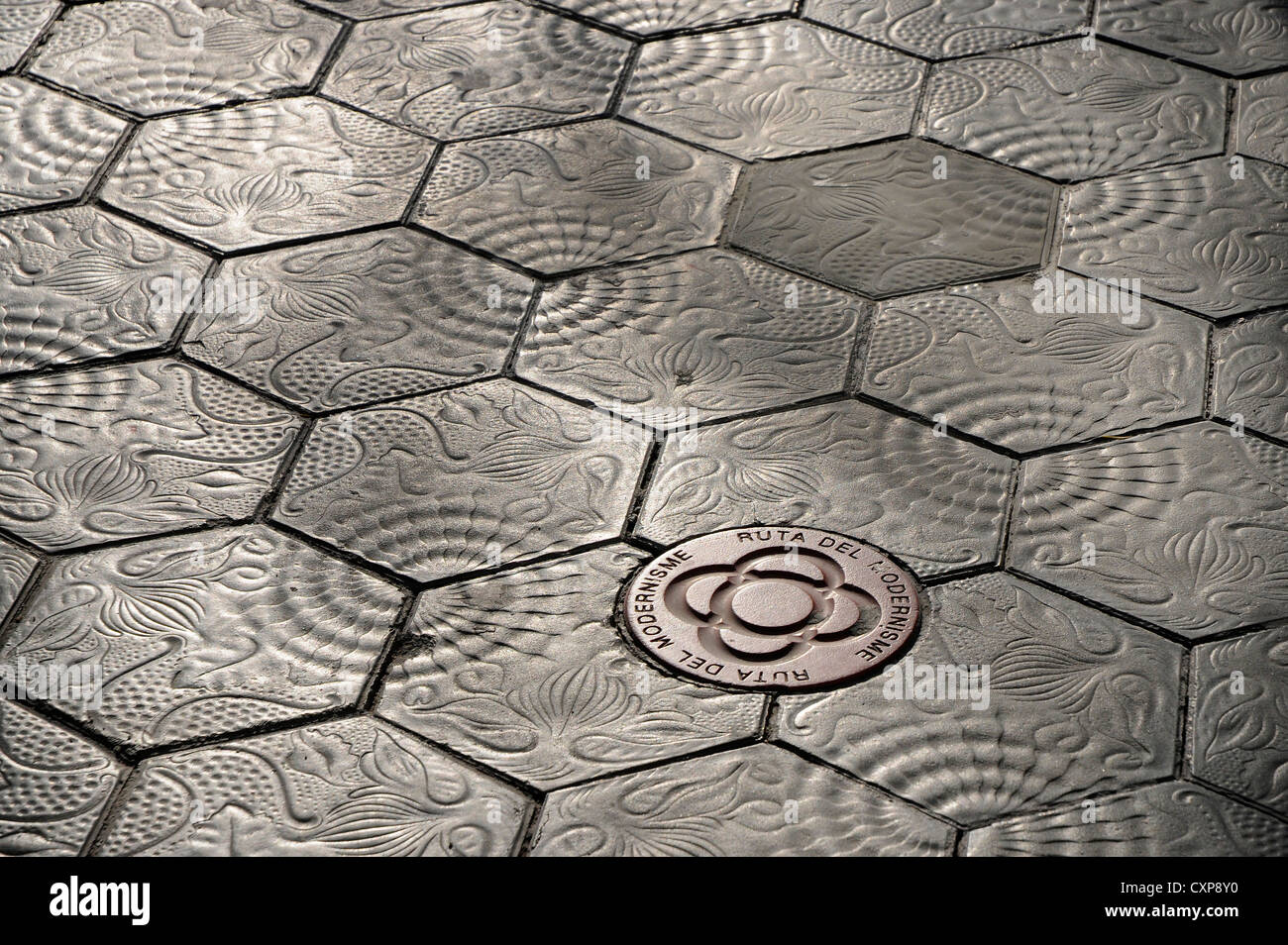 indication of the route of modernism on the pavers floor tiles hexagonal on the floor of  Paseo de Gracia in Barcelona - Stock Image