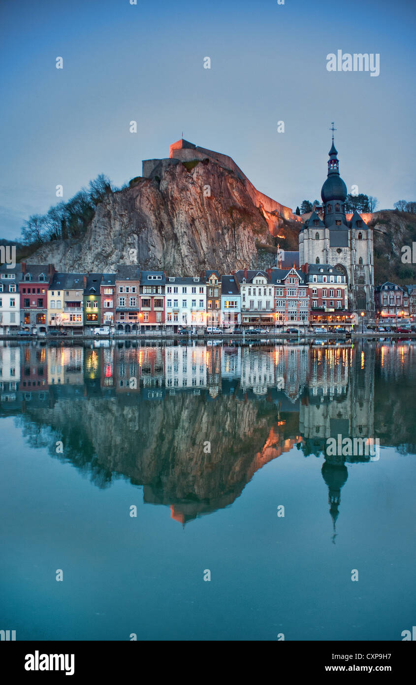 Houses, shops, a church and a fortress are reflected in the Meuse river at dusk in the Belgian town of Dinant in - Stock Image