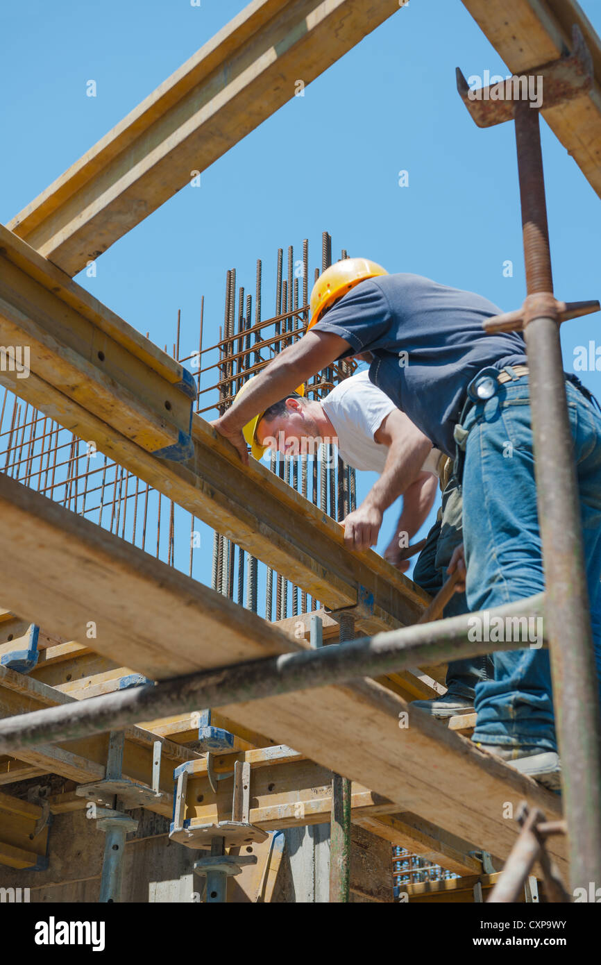 Construction workers placing formwork beams - Stock Image