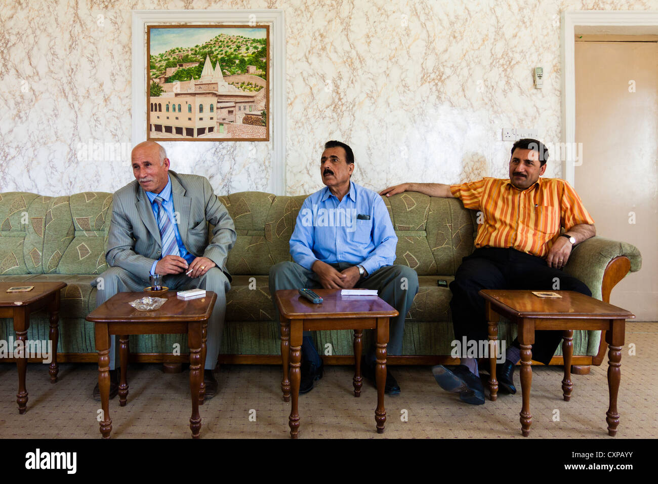 Mr Pir Khidir Sulayman (left) member of the Kurdish Parliament and director of the Lalish Cultural Center sits at - Stock Image