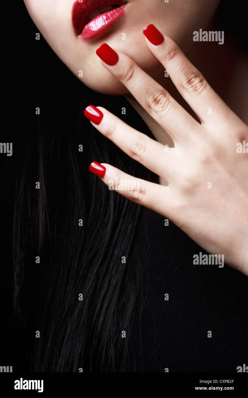 Close up of womans red nails, lips and long black hair Stock Photo ...
