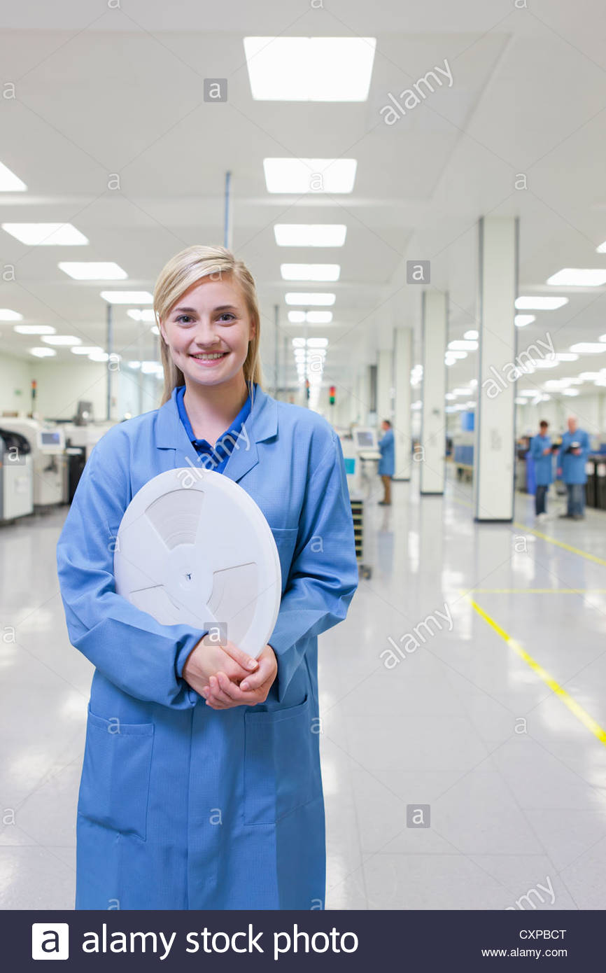 Portrait of smiling technician in lab coat holding data tape in hi-tech manufacturing plant - Stock Image