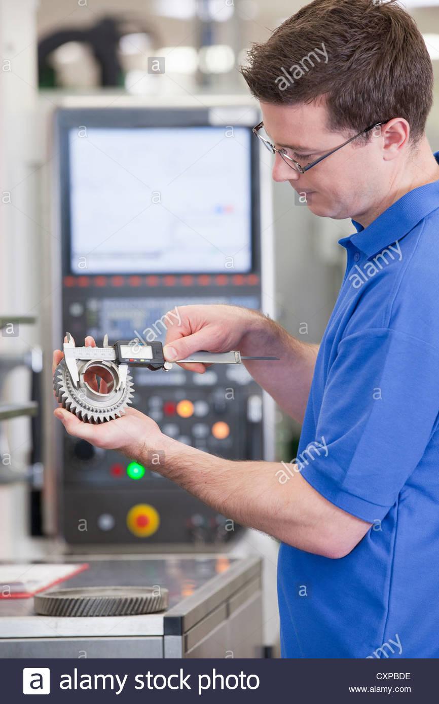 Technician measuring gear wheel with vernier caliper in front of lathe cutting machine in hi-tech manufacturing - Stock Image
