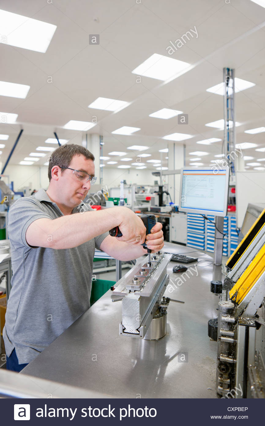 Technician assembling product in hi-tech manufacturing plant Stock Photo