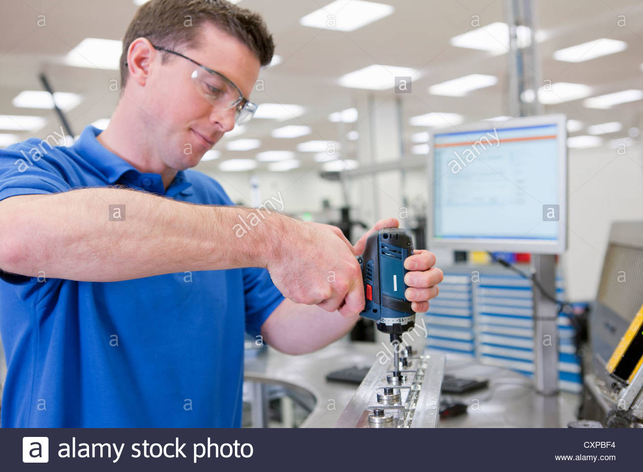 Technician assembling product in hi-tech manufacturing plant - Stock Image