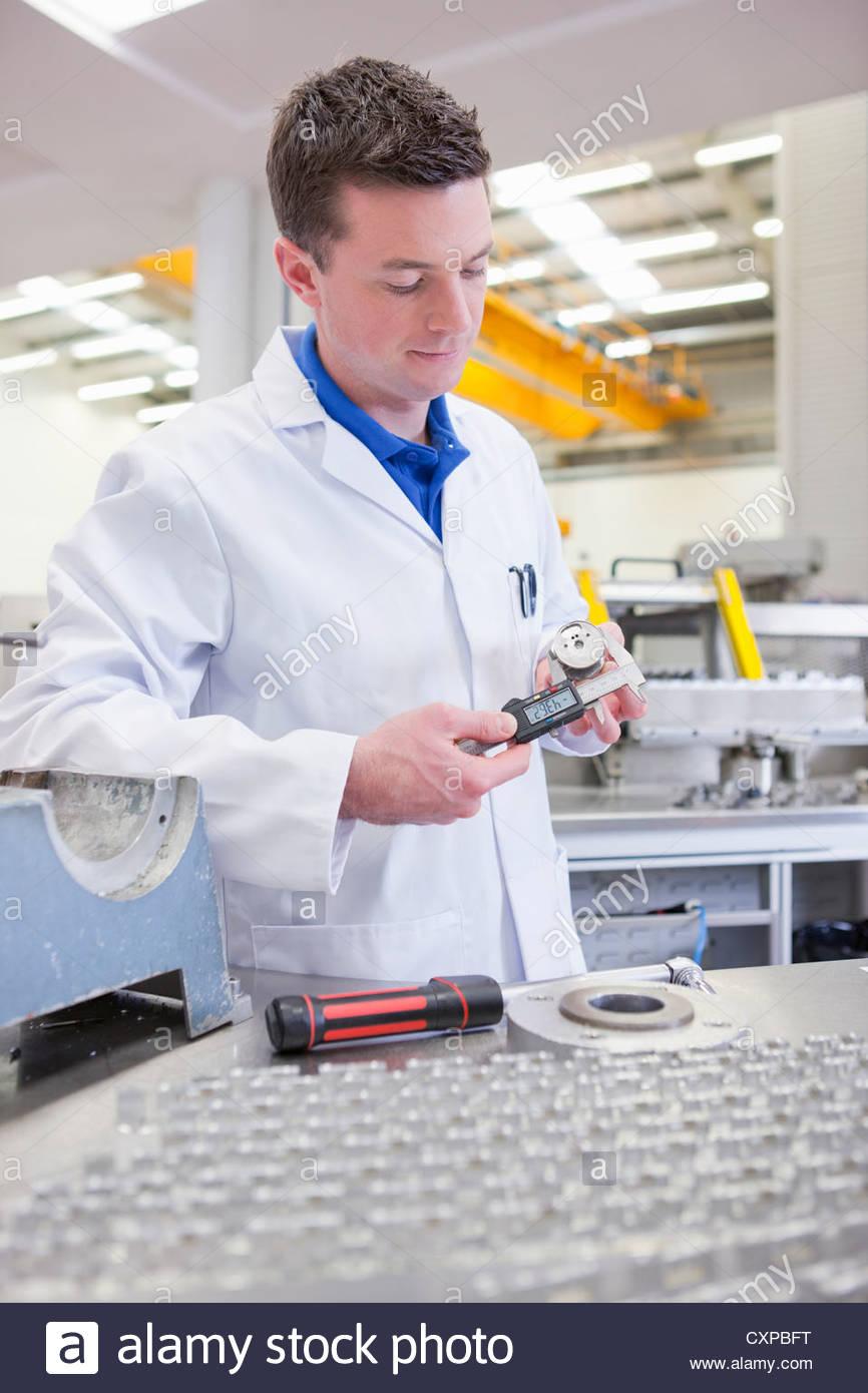 Scientist measuring aluminum product with vernier caliper in hi-tech manufacturing plant - Stock Image