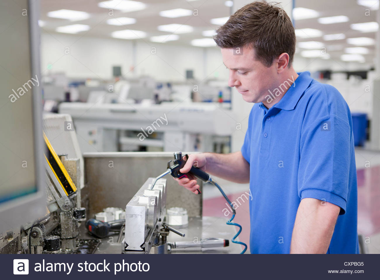 Technician working with aluminum products in hi-tech manufacturing plant - Stock Image