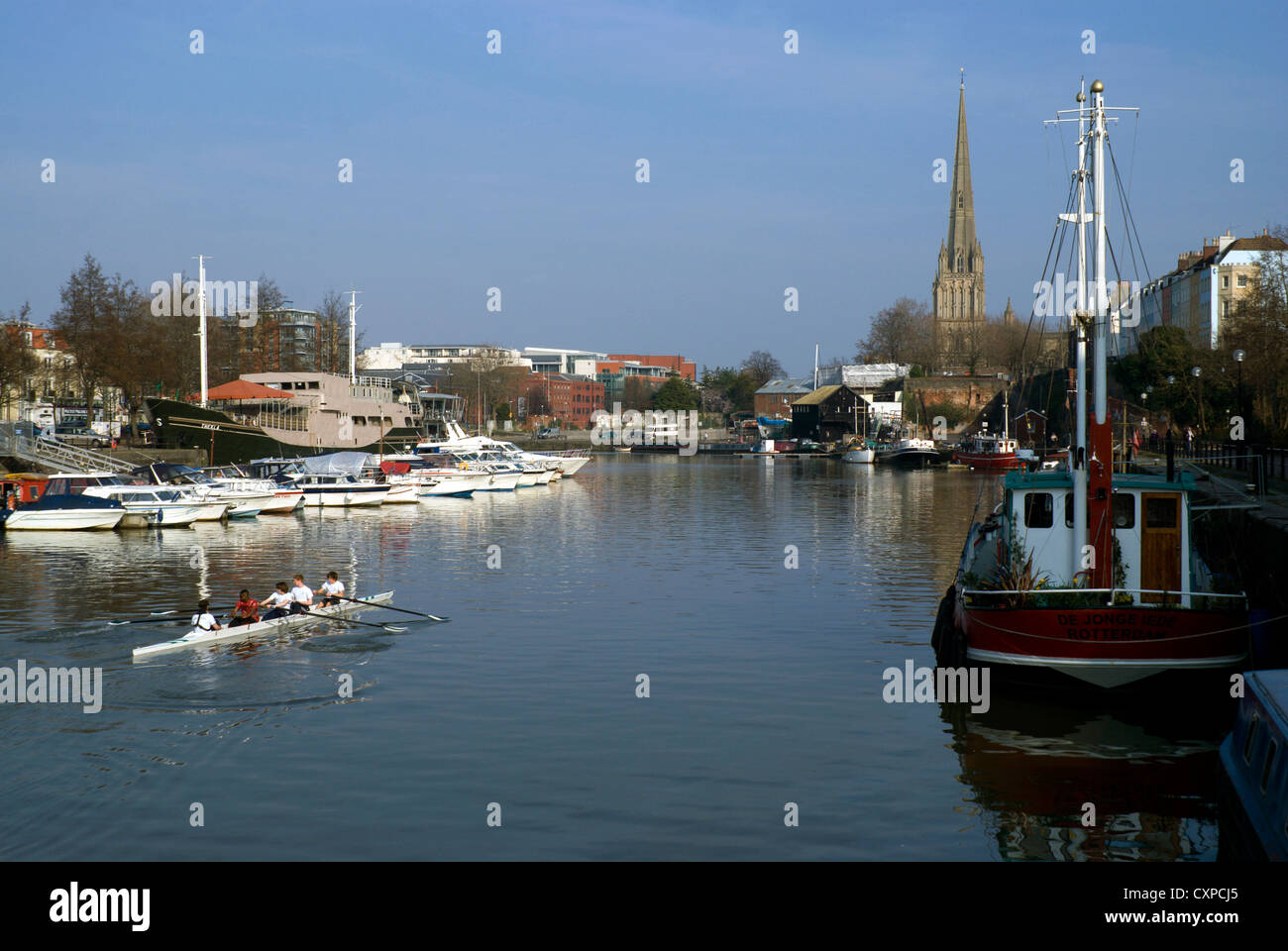 rowers floating harbour bristol with the spire of st mary redcliffe in distance uk - Stock Image