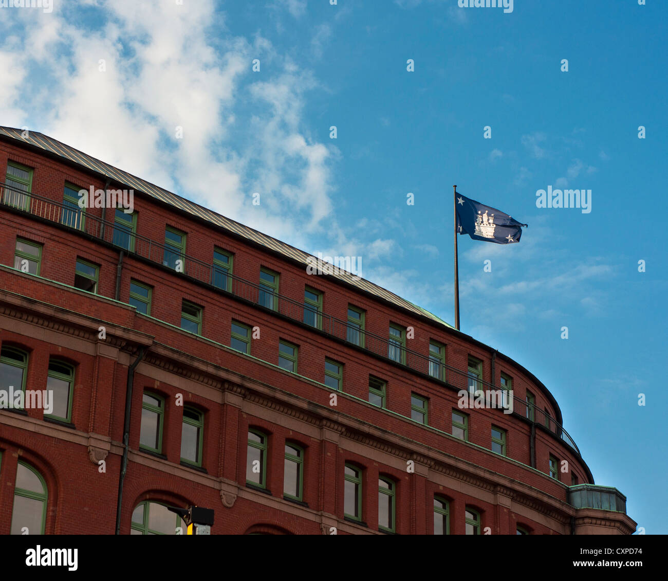 Flag of Free and Hanseatic City of Hamburg (Freie und Hansestadt Hamburg), flying and wavering high on the building. Stock Photo