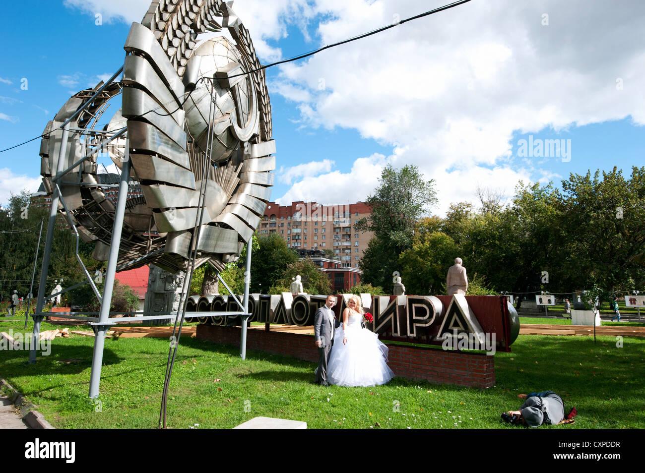Photo shoot of a bridal couple in front of a hammer and sickle monument in the sculpture park of Moscow, Russia. - Stock Image