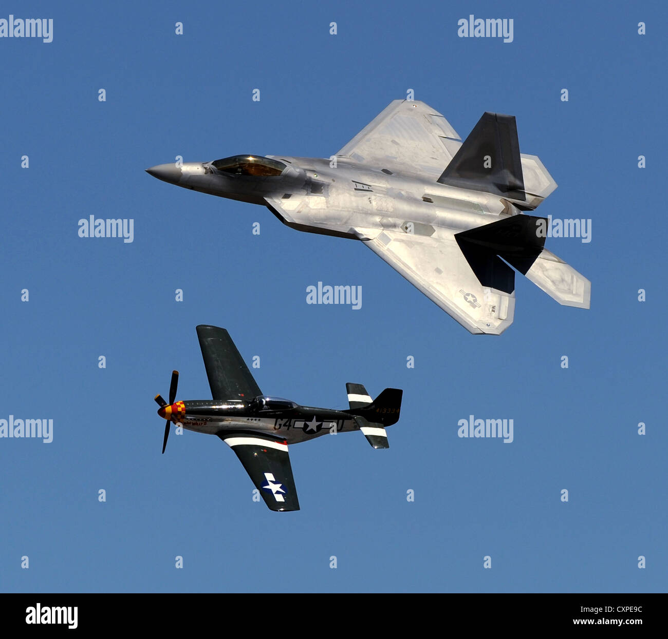 A vintage P-51 Mustang fighter aircraft and a US Air Force F-22 Raptor fighter aircraft perform a heritage flight - Stock Image