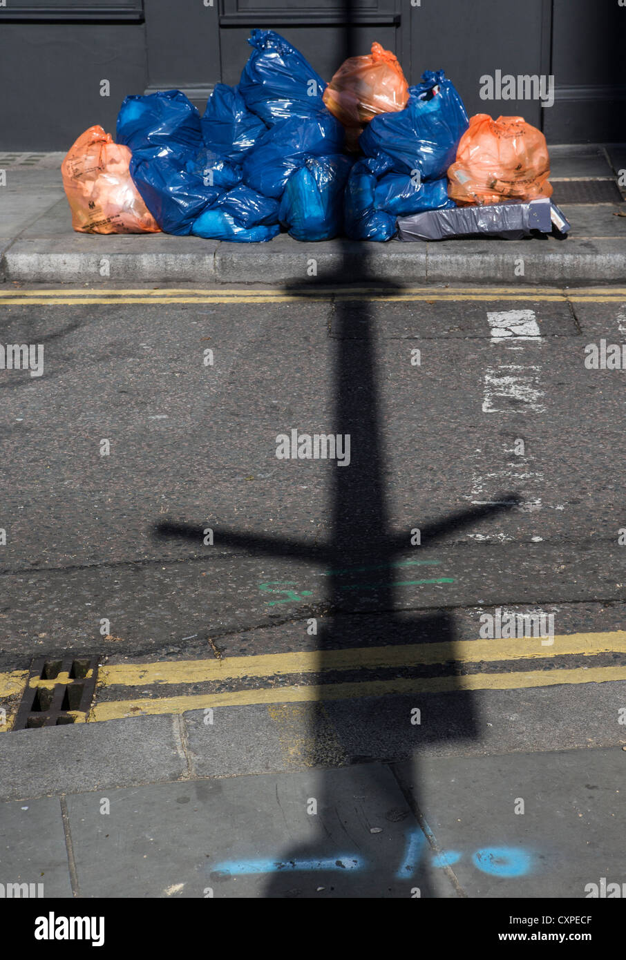 The shadow of a lamp-post falling across an empty street, and over a pile of blue and orange refuse sacks - Stock Image