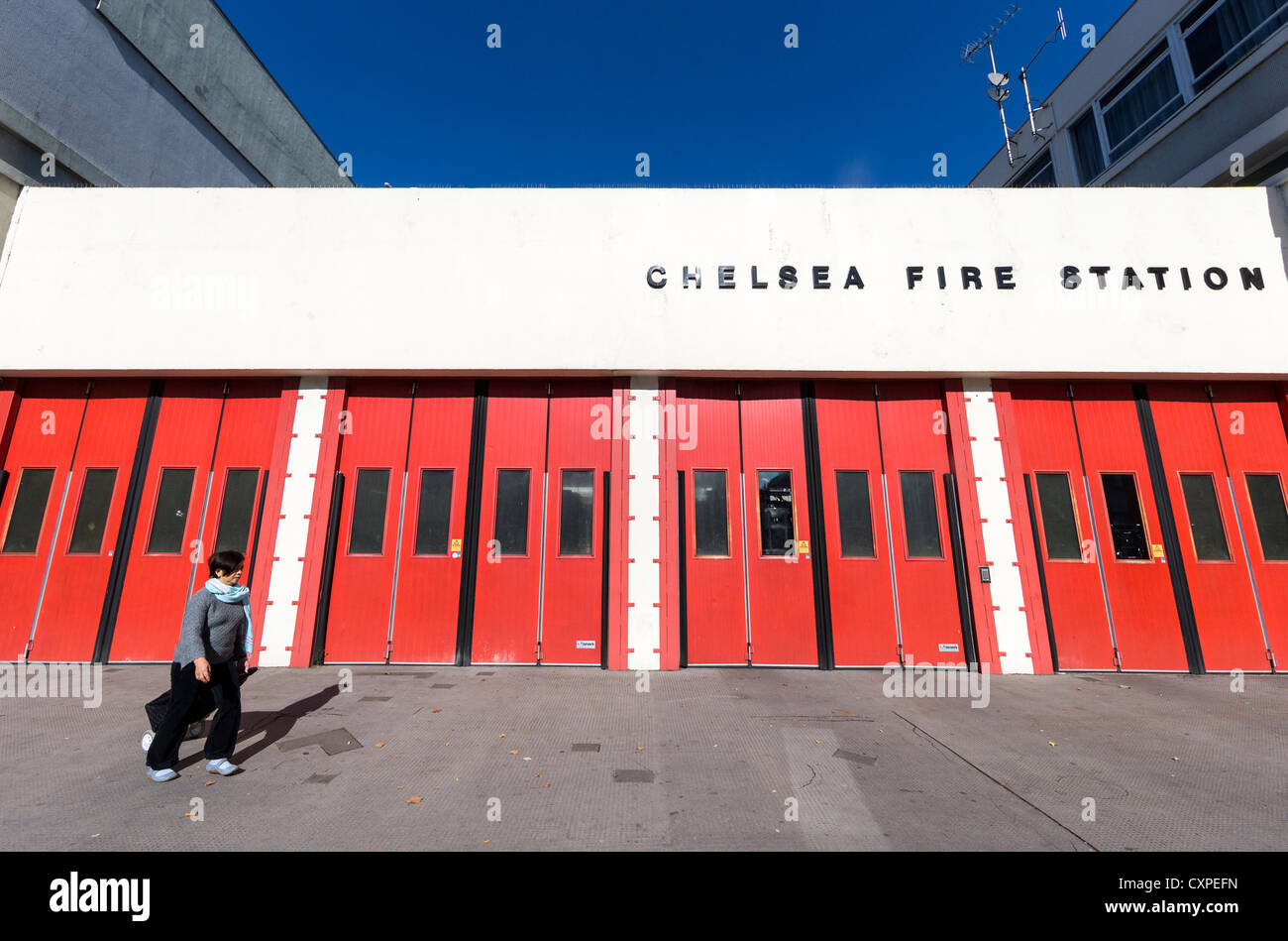 A woman walking past the red doors of Chelsea Fire Station in London's Kings Road - Stock Image