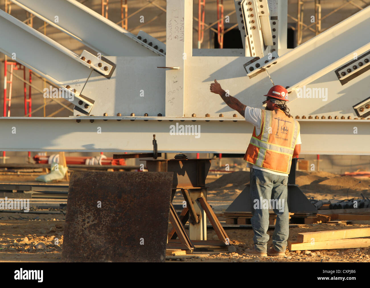 A construction worker guides one of two cranes preparing to lift a 335,000 pound box truss during the construction - Stock Image