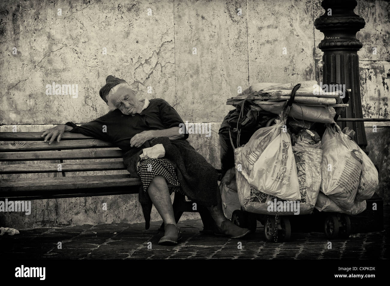 Old lady tramp on bench in Rome, Italy. - Stock Image