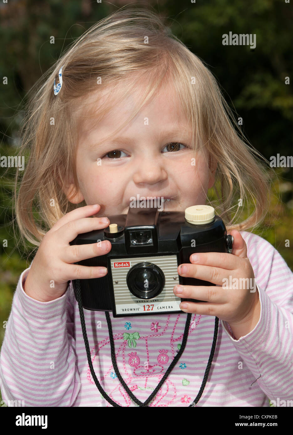 Young girl playing with Kodak Brownie camera. - Stock Image