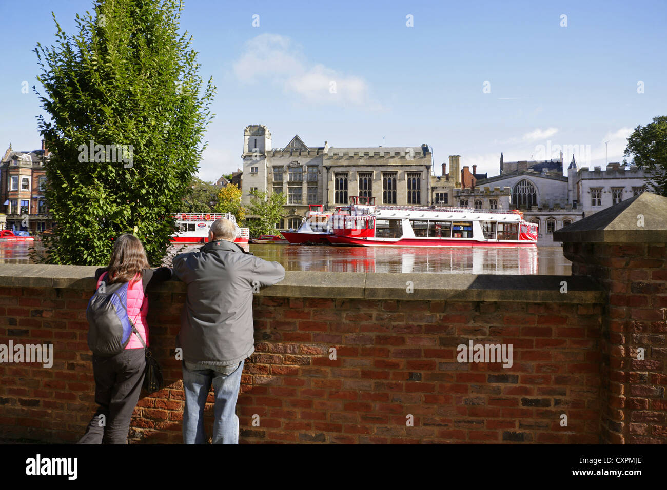 Tourists look over flood defence barriers at the flooded River Ouse, York, and the historic Guildhall. Stock Photo