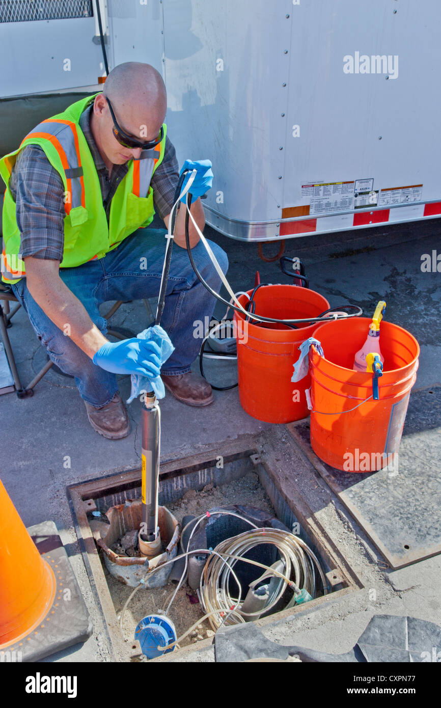Technician preparing to lower  'bladder pump'  to test for groundwater contamination. - Stock Image