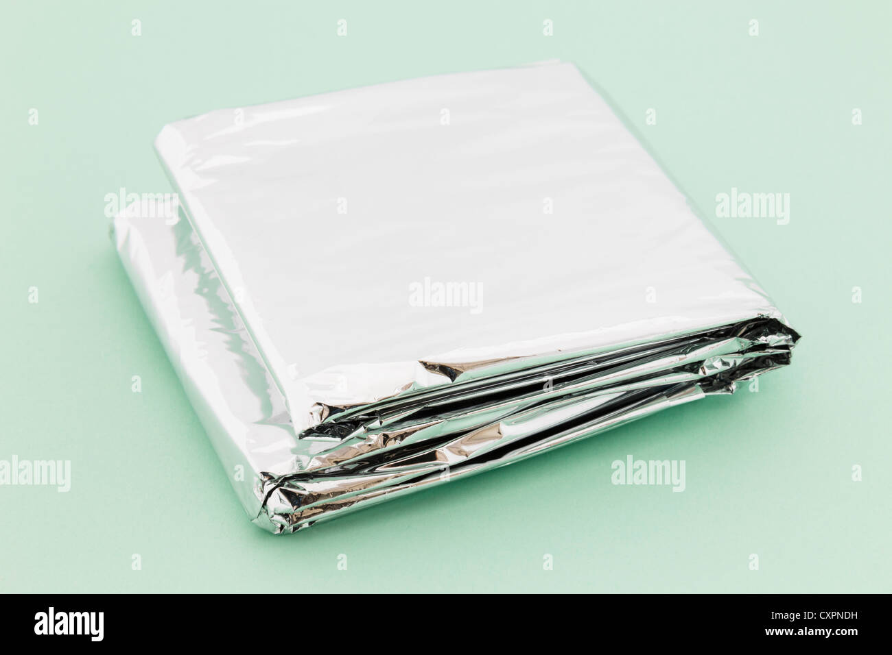 843699c306 Insulating foil emergency blanket folded up on a green background - Stock  Image