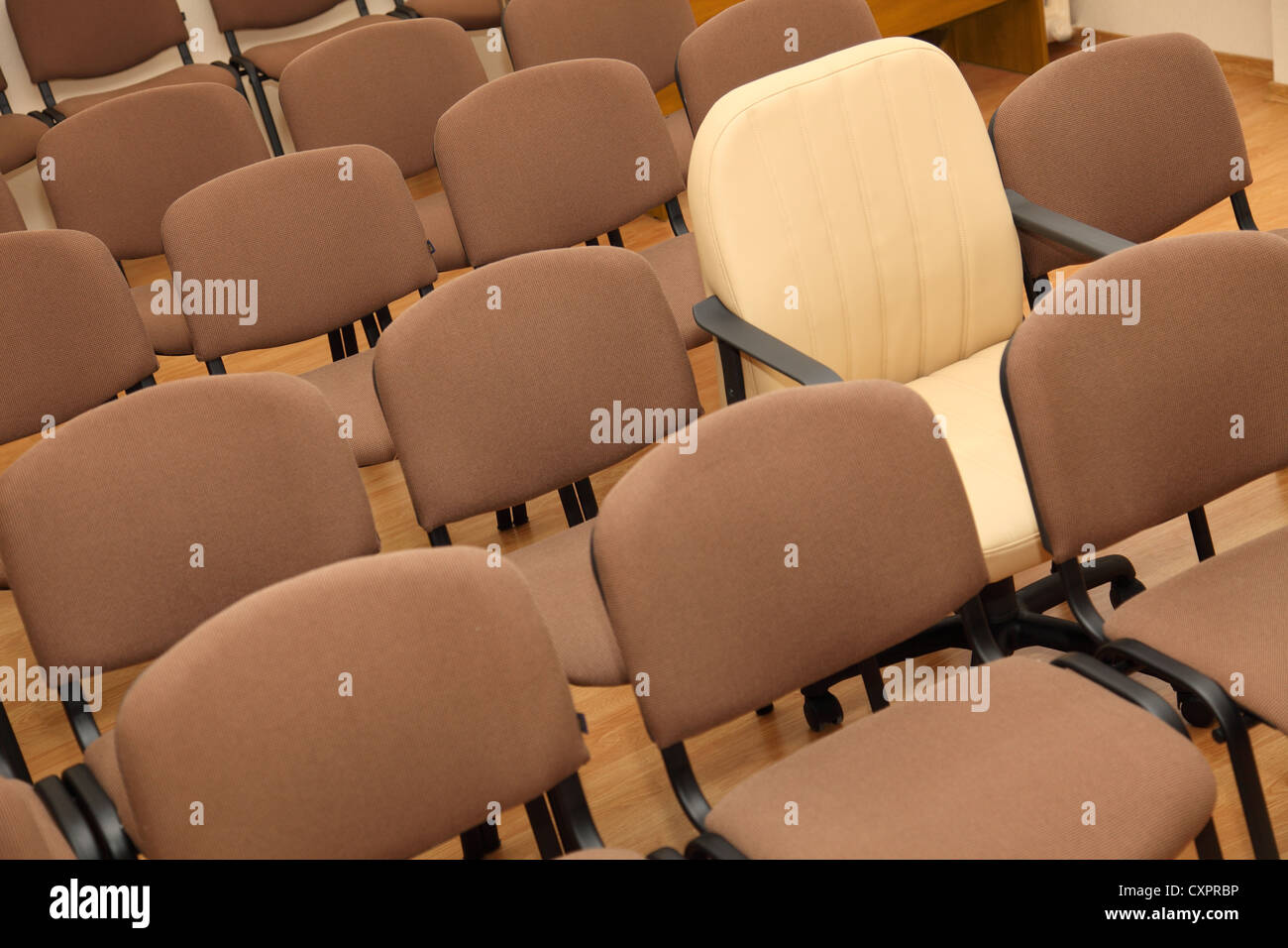Manager chair stands out among the rows of ordinary office chairs - Stock Image