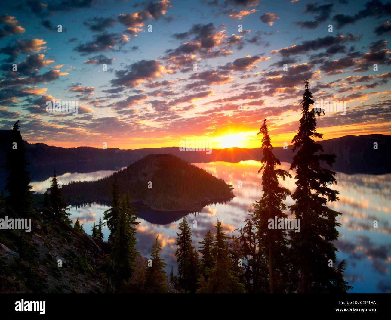 Sunrise on Crater Lake with Wizard Island. Crater Lake National Park. Oregon reflection,sun,silhouette,forest, - Stock Image