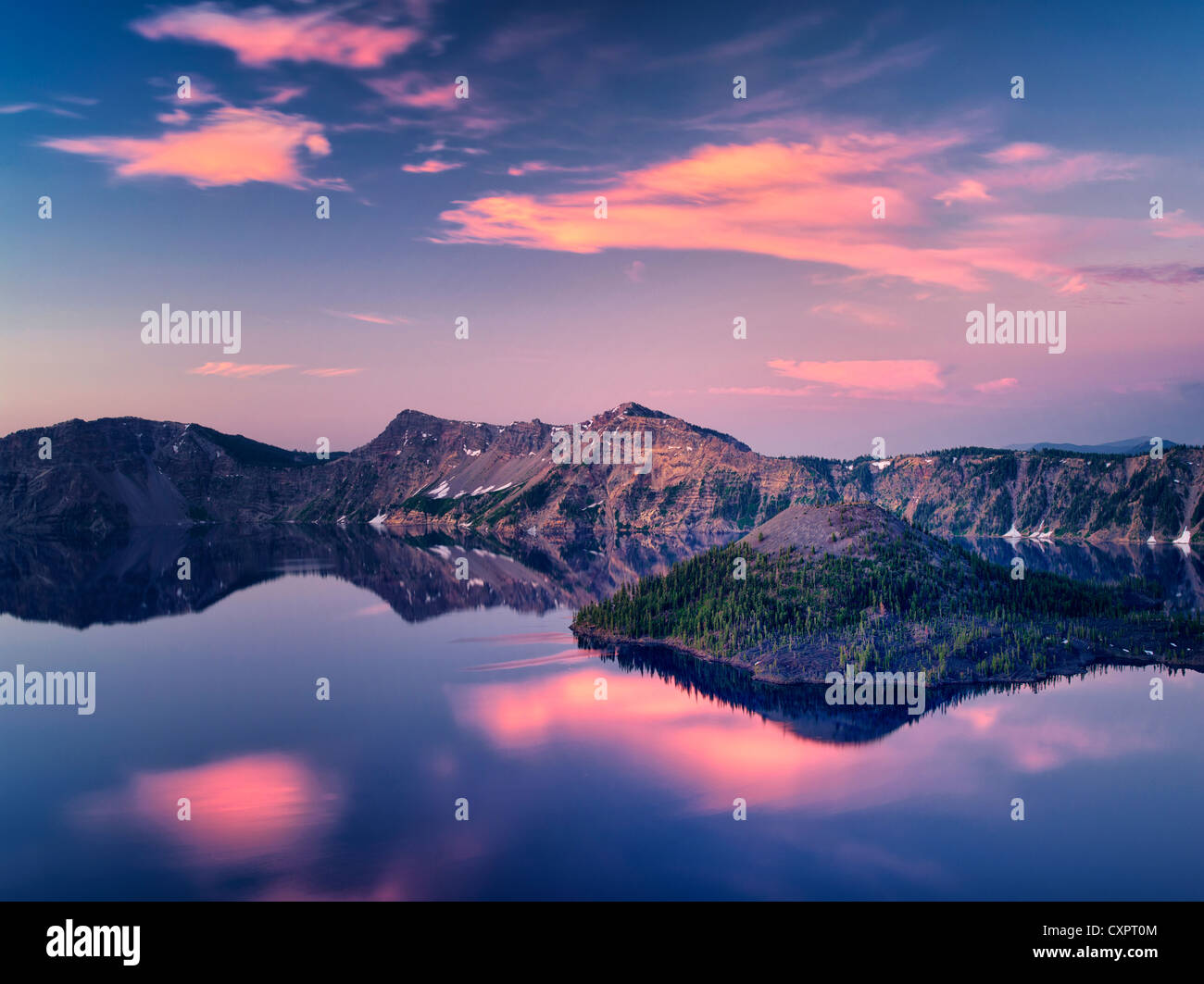 Crater Lake with Wizard Island at sunrise . Crater Lake National Park, Oregon, sunrise clouds reflecting in calm Stock Photo