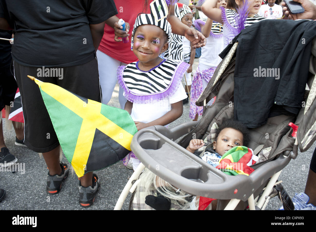 Caribbean Kiddies Day parade, Crown Heights. Costumed, young girl holding Jamaican flag. Parade is part of Labor - Stock Image