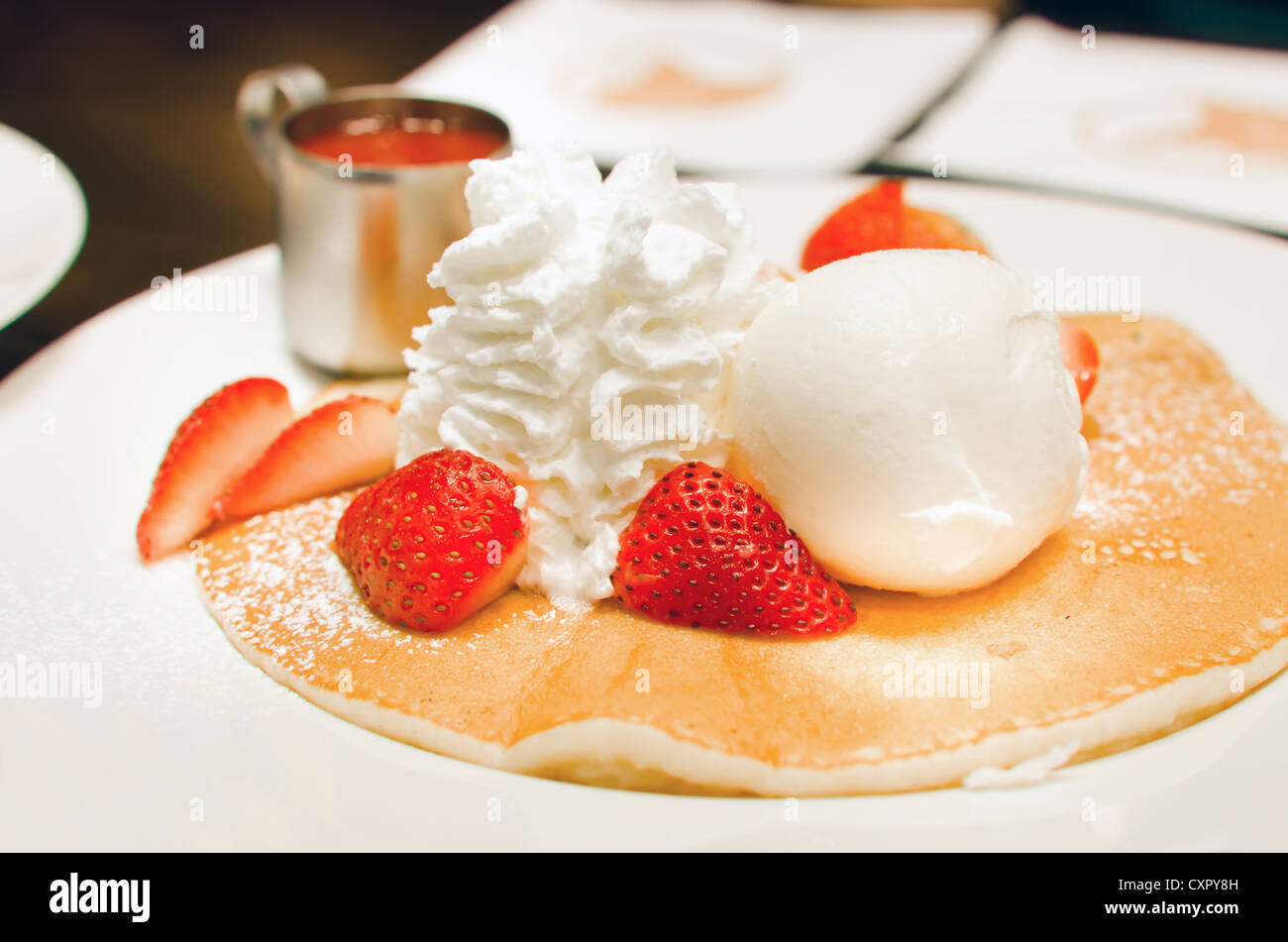 pancakes with strawberries and whipping cream , ice cream . - Stock Image