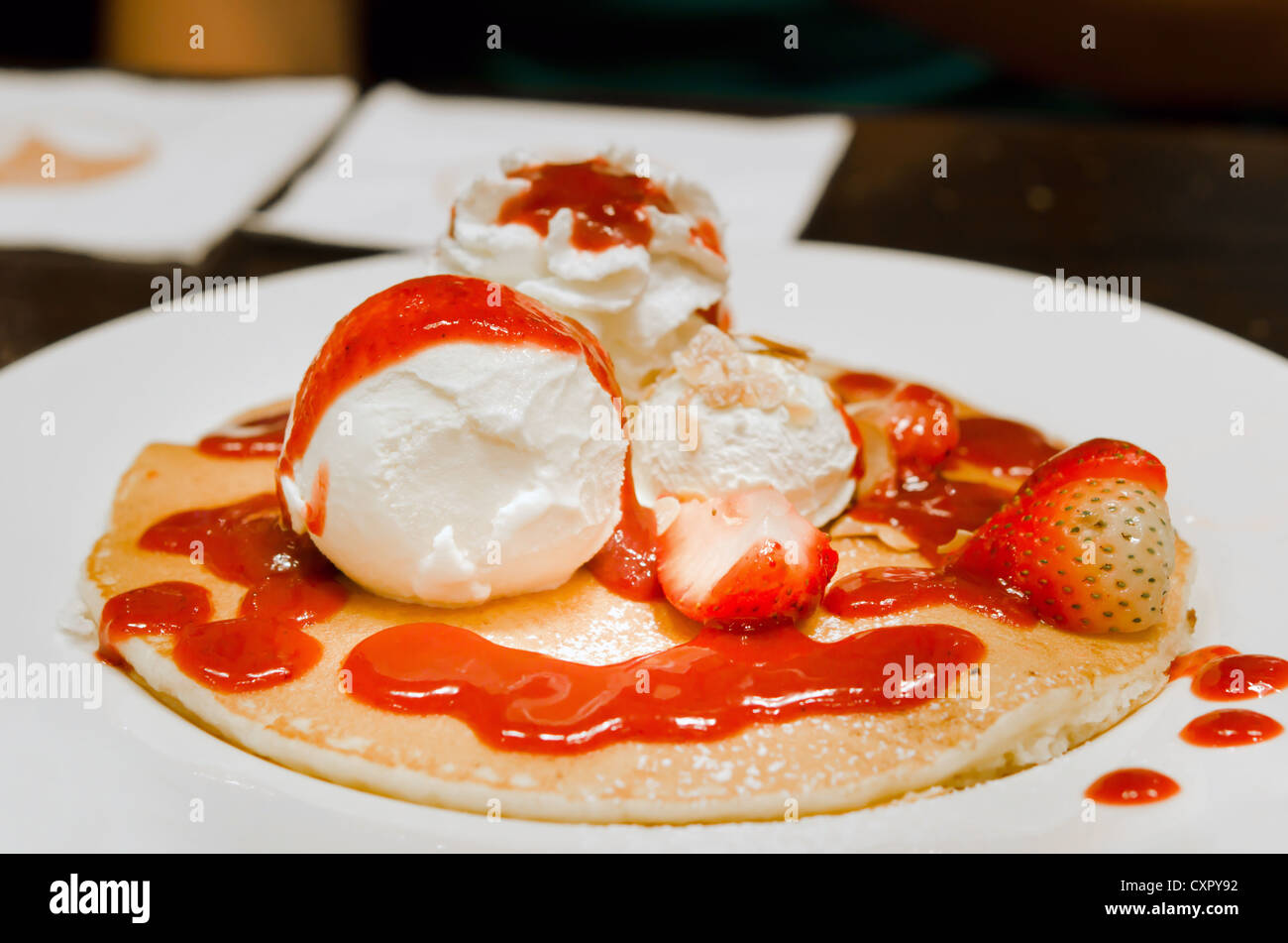 pancakes with whipping cream , ice cream , fresh strawberries and syrup . - Stock Image