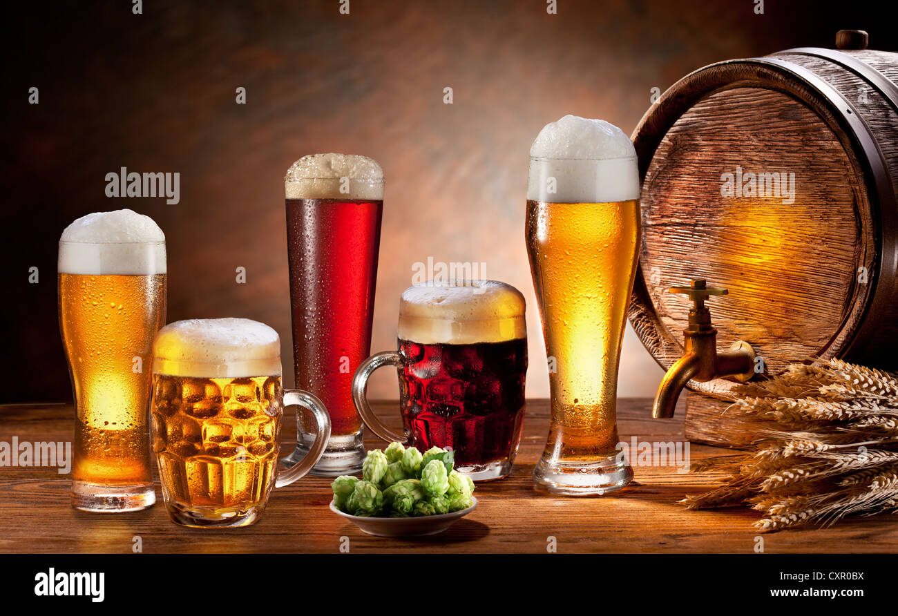Beer barrel and draft beer by the glass. Dark background. - Stock Image
