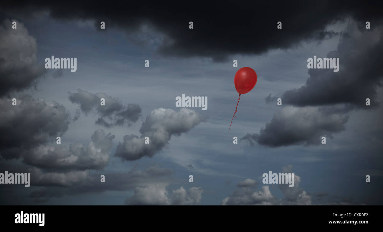 Red balloon floating through dark sky - Stock Image