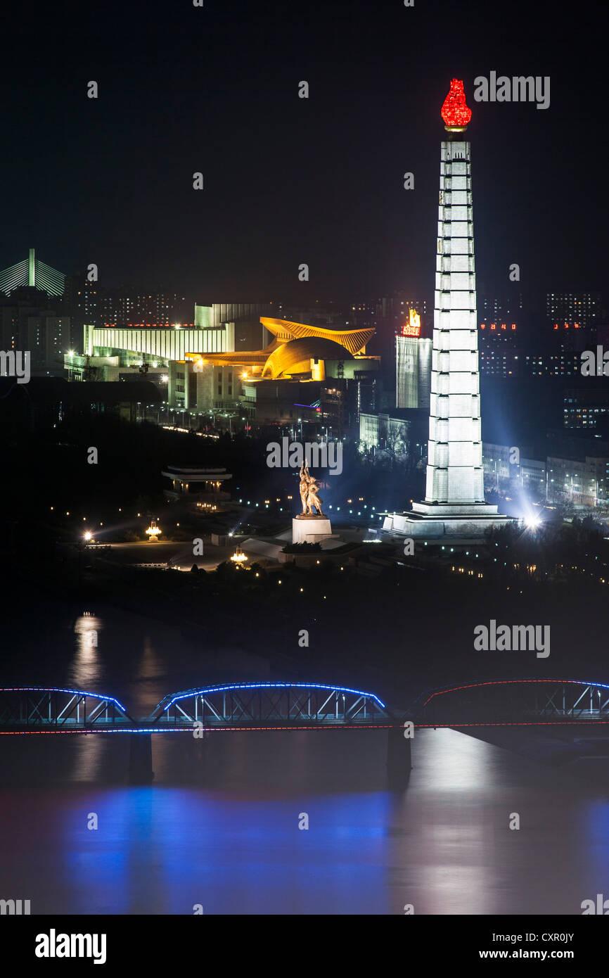 Democratic Peoples's Republic of Korea (DPRK), North Korea, Pyongyang, Juche Tower and Taedong river illuminated - Stock Image