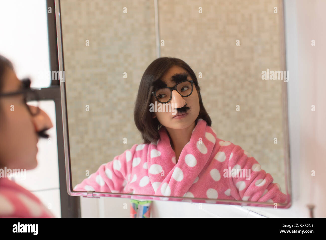 Young woman looking herself wearing funny disguise - Stock Image