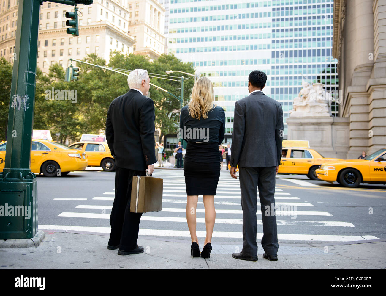 Rear view of three businesspeople at crossing on a New York City street - Stock Image