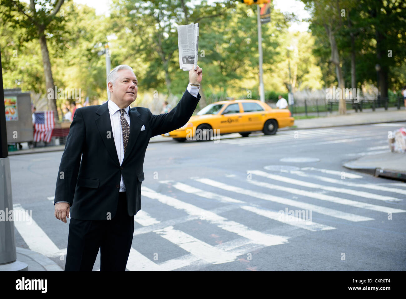 Businessman hailing a cab in New York City - Stock Image