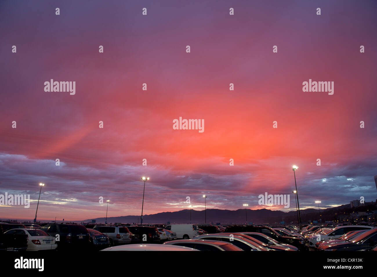 Cars in parking lot at sunset - Stock Image
