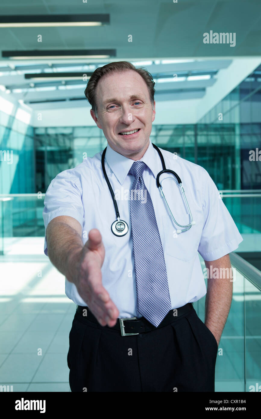 Portrait of doctor shaking hands, personal perspective - Stock Image