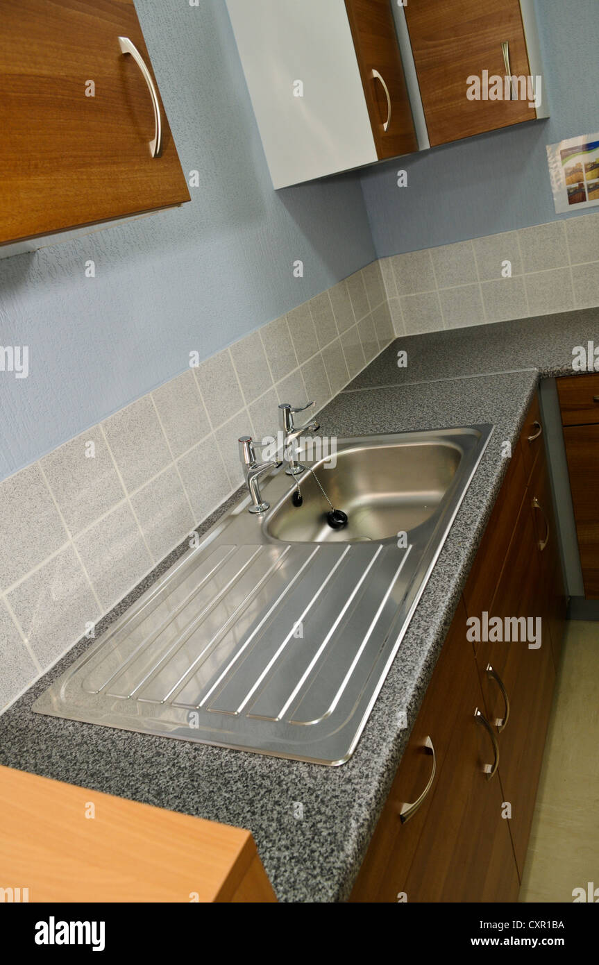 Boring stainless steel kitchen sink and dull wooden kitchen ...