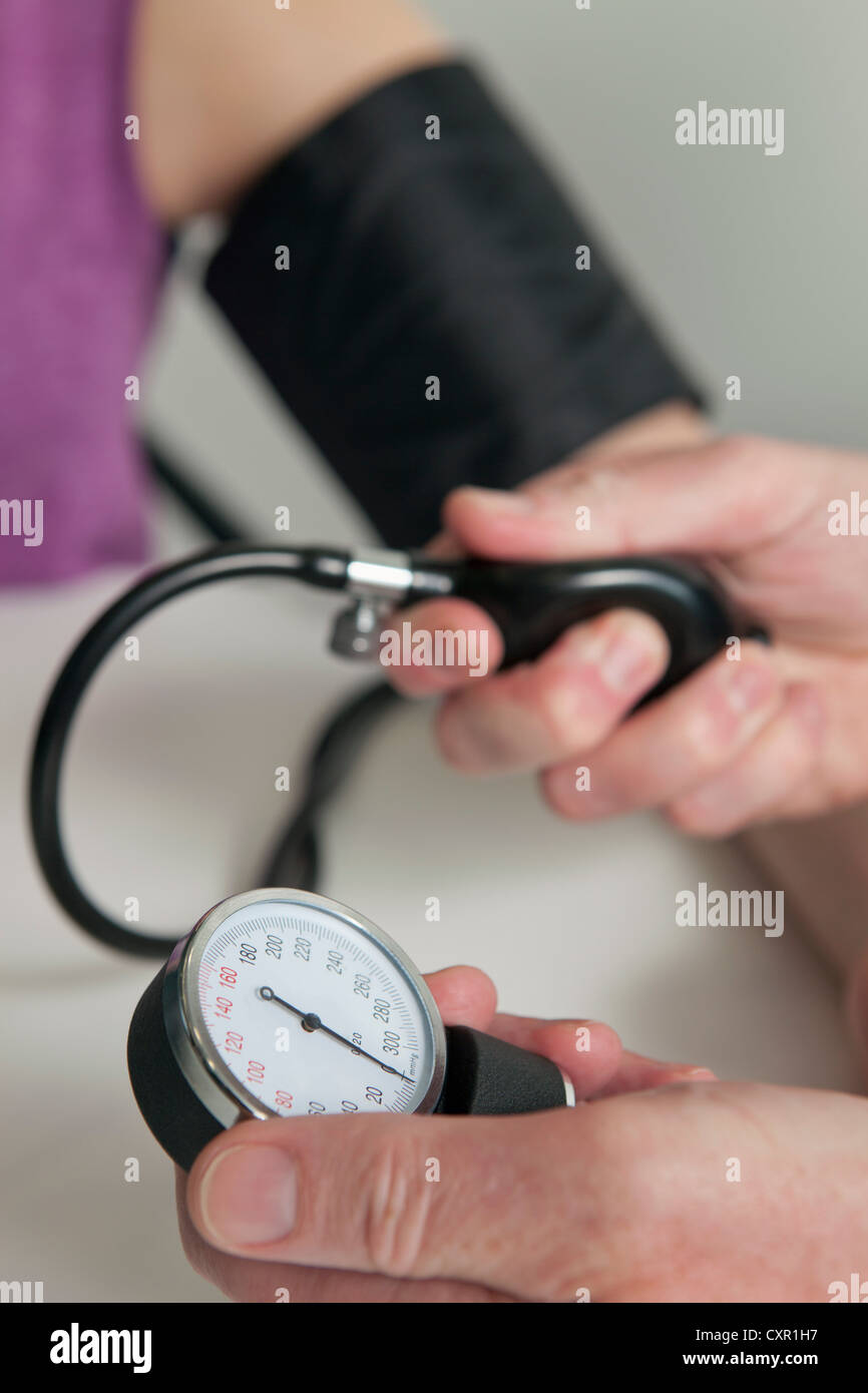 Doctor using blood pressure gauge on patient during medical examination - Stock Image