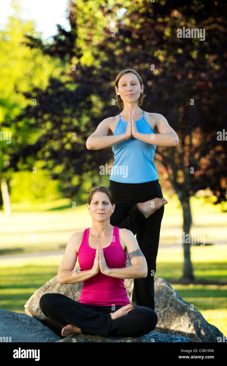 Two women in yoga poses on rocks - Stock Image