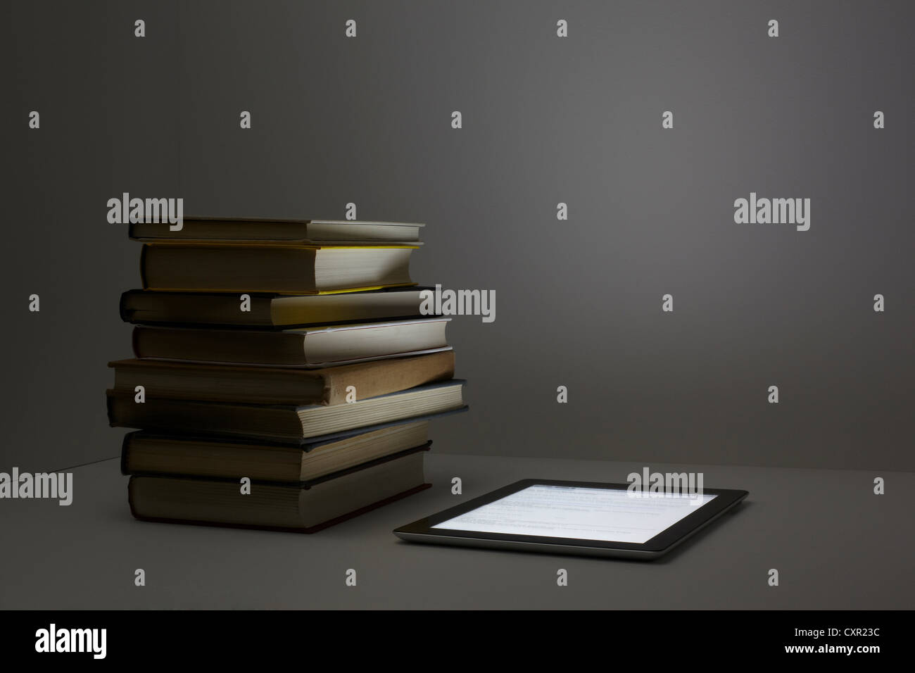 Stack of books with digital tablet - Stock Image